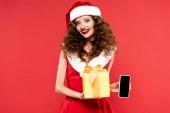 atraktivní usmívající se dívka v kostýmu Santa drží vánoční dárek a smartphone s prázdnou obrazovkou, izolované na červené