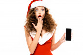 überrascht Mädchen im Weihnachtsmannkostüm zeigt Smartphone mit leerem Bildschirm, isoliert auf weiß
