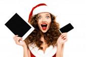 vzrušená kudrnatá žena v kostýmu Santa držící digitální zařízení s prázdnými obrazovkami, izolovaná na bílém