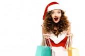meglepett lány télapó jelmez pózol bevásárló táskák, elszigetelt fehér