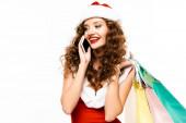 Lächelndes, lockiges Mädchen im Weihnachtsmannkostüm, das Einkaufstüten in der Hand hält und auf dem Smartphone spricht, isoliert auf weiß