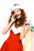 krásná kudrnatá dívka v kostýmu Santa drží nákupní tašky a mluví na smartphone, izolované na bílém