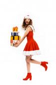 schönes Mädchen im Weihnachtsmannkostüm läuft mit einem Stapel von Geschenken, isoliert auf weiß