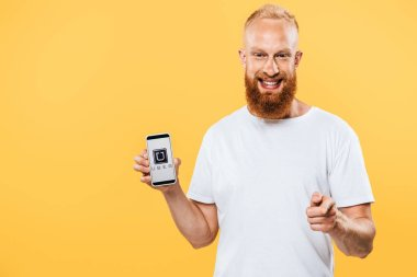 KYIV, UKRAINE - AUGUST 27, 2019: smiling bearded man presenting smartphone with uber app and pointing at you, isolated on yellow stock vector