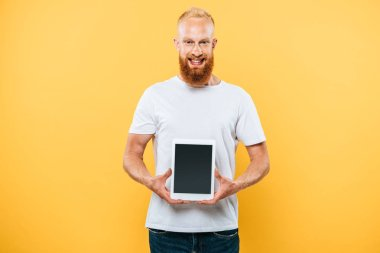 Cheerful man showing digital tablet with blank screen, isolated on yellow stock vector