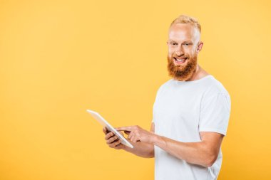 Cheerful bearded man using digital tablet, isolated on yellow stock vector