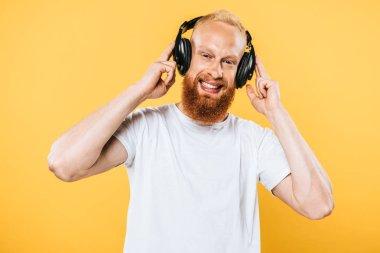 Cheerful beard man listening music with headphones, isolated on yellow stock vector