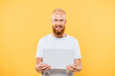 Happy bearded man using laptop, isolated on yellow stock vector
