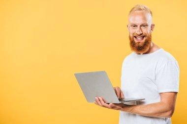 Smiling bearded man using laptop, isolated on yellow stock vector
