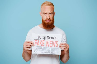 Upset bearded man showing newspaper with fake news, isolated on blue stock vector
