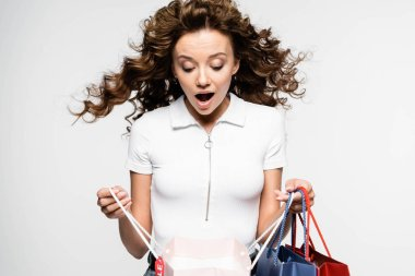Surprised curly girl looking into shopping bags, isolated on white stock vector