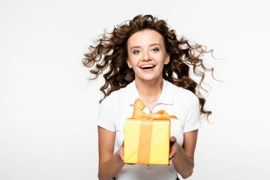 Attractive curly girl holding yellow gift box, isolated on white stock vector