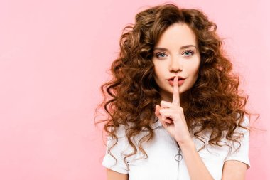 beautiful curly girl showing silence symbol, isolated on pink