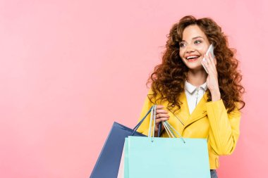 Beautiful curly girl holding shopping bags while talking on smartphone, isolated on pink stock vector
