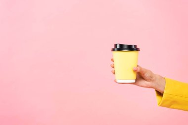 Cropped view of woman holding yellow disposable cup of coffee, isolated on pink stock vector