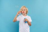 dítě v bílém tričku foukání mýdlové bubliny na modrém pozadí