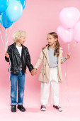 smiling kids holding balloons and holding hands on pink background