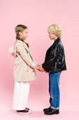 side view of kids holding hands on pink background
