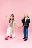 dítě na koni penny palubě a chlapec ukazující ano gesto na růžovém pozadí
