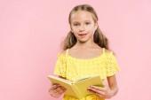 Lächelndes Kind hält Buch in der Hand und blickt isoliert in die Kamera auf rosa