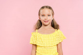 smiling and cute kid looking at camera isolated on pink