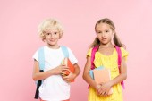 smiling schoolchildren with backpacks holding books isolated on pink