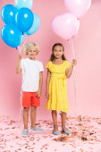 smiling and cute kids holding balloons on pink background