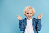 smiling and shocked kid with outstretched hands looking at camera isolated on blue