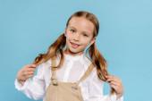 lächelndes und nettes Kind, das in die Kamera schaut und Haare auf blauem Grund berührt