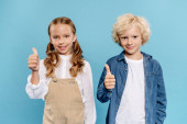 usmívající se a roztomilé děti při pohledu na kameru ukazuje rád izolované na modré