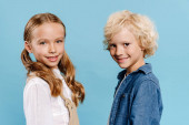 smiling and cute kids looking at camera isolated on blue