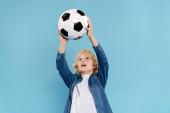 roztomilé dítě hrát s fotbalem izolované na modré s kopírovacím prostorem