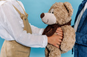 Photo cropped view of kids holding teddy bear isolated on blue