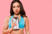 attraktives Mädchen im Badeanzug hält Schokoladenriegel isoliert auf rosa