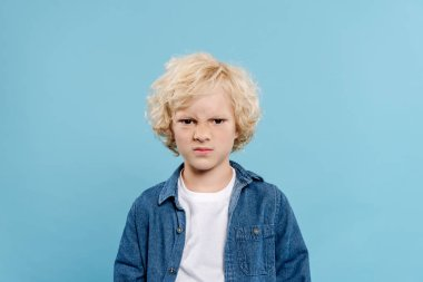 Irritated and cute kid looking at camera isolated on blue stock vector