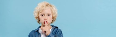 panoramic shot of cute kid showing secret gesture and looking at camera isolated on blue