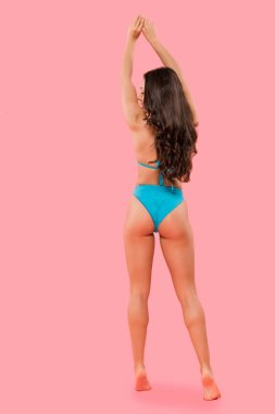 sexy woman in swimsuit standing with hands above head isolated on pink