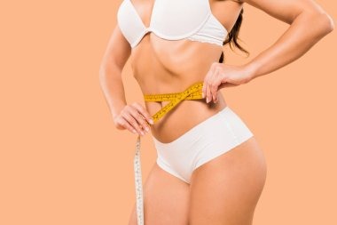 cropped view of woman in underwear measuring waist isolated on beige