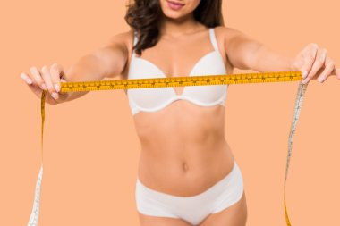 cropped view of woman in underwear holding measuring tape isolated on beige