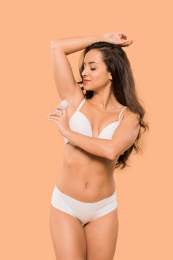 cheerful woman applying deodorant roll on isolated on beige
