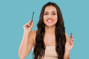 happy woman holding mascara and smiling isolated on blue