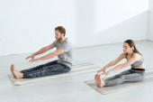 young man and woman practicing yoga in seated forward bend pose