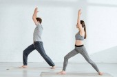 side view of young man and woman practicing yoga in warrior I pose