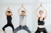 junge Männer und Frauen praktizieren Yoga in Göttin-Pose mit erhobenen Gebetshänden
