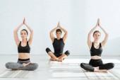 Fotografie junge Frauen und Männer praktizieren Yoga in halber Lotus-Pose mit erhobenen Gebetshänden