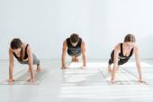 fiatal nők és férfi gyakorló jóga deszka pózban