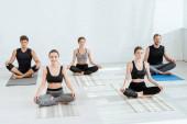 Fotografie Fünf junge Leute praktizieren Yoga in halber Lotus-Pose