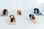 Fotografie Fünf junge Leute praktizieren Yoga in Großkindpose