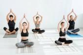 öt fiatal fél lótuszban meditál felemelt imádkozó kezekkel.