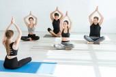 pohled zezadu na instruktora jógy ukazujícího mladým lidem poloviční lotosovou pózu se zvednutými modlitebními rukami